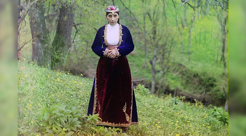 An Armenian woman in national costume poses for Prokudin-Gorskii on a hillside near Artvin